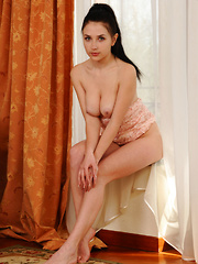 Niemira bares her smooth, plump pussy as she poses on the couch.