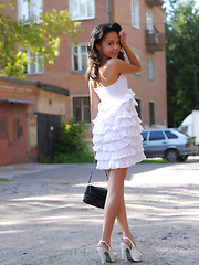 Adorable dark haired teen chick demonstrating her excellent body under white dress outdoors.