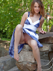 One could easily get stunned and hypnotized in Nikia\'s sparkling, sexy eyes with seductive gaze as she strips her blue dress and poses naughtily all over the garden.