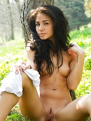 Fresh and exotic beautiful Malina relaxes amongst the lush grass and trees.
