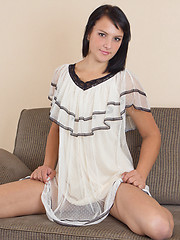 Delightful dark haired bombshell undressing and demonstrating natural pussy on the sofa.