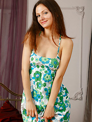 Zhanet strips off her flowery dress and   poses sensually on the bed spreading her   sexy legs in front of the camera.