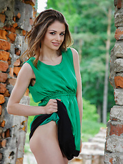 Loretta strips her green sexy flowing dress and flaunts her lean, nubile body and delectable pussy by the brick wall ruins.