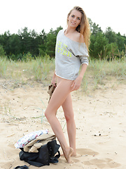 Winsome long haired teen cutie taking off clothes and showing appetizing body on the shore. Girl on the seaside
