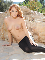 Lucy Anne strips from her tight black pants and pink top outdoors
