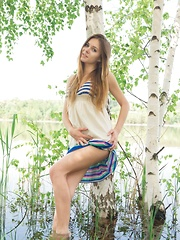 Katie A playfully wades into the lake while undressing her dress, showing off her athletic, slender body.