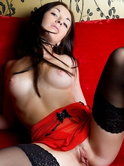 Night A's lean legs garbed in sheer black stockings while her body is wrapped in silky red lingerie dress as she poses sensually on top of the sofa