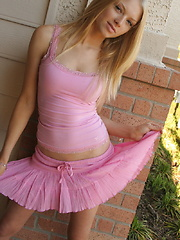 Cute blonde teen Skye teases with her perky tits outside in her pink top and short skirt with a black g-string underneath