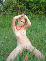 The tall green grass makes this shapely blondes body stand out even more as she poses on the lap of nature.