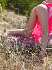 Brunette lays on the ground in the hot sunshine while she reveals every bit of her stunning sexiness.